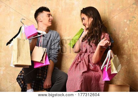 smiling happy couple of pretty cute fashionable woman with long brunette curly hair and young handsome guy holds hangers and colorful shopping bags on beige background