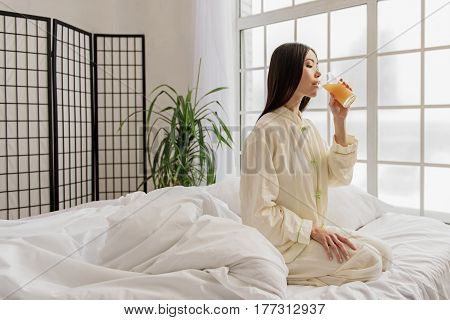 Calm young female drinking delicious juice while sitting on soft bed