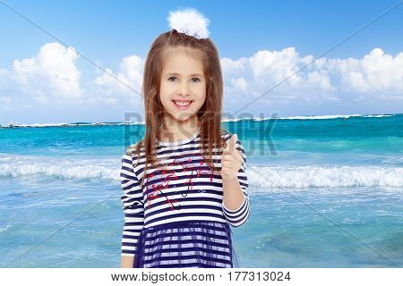 Beautiful little girl long hair and white bow on her head , in a summer dress in stripes.She raised her thumb up . Gesture All right.White sand , blue sea and blue sky with clouds.