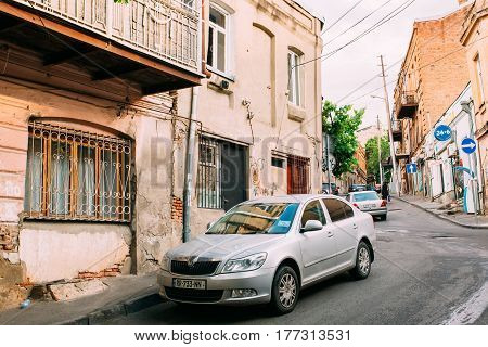 Tbilisi, Georgia - May 20, 2016: The View Of Parked Silvery Skoda Octavia Car Near The Shabby Building On Narrow Uphill Street In Summer Day Under Somber Sky.