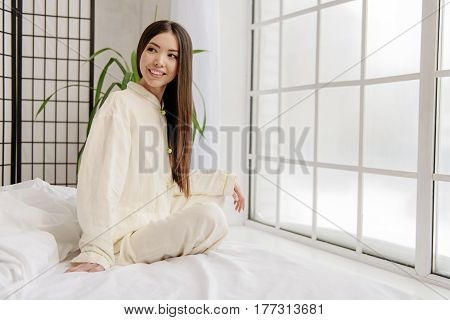 Side view of portrait of asian woman expressing pleasure while looking away. Good feeling concept