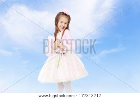 Dressy little girl long blonde hair, beautiful pink dress and a rose in her hair.She pulls my hand through my hair.On the background of summer blue sky and fluffy clouds.
