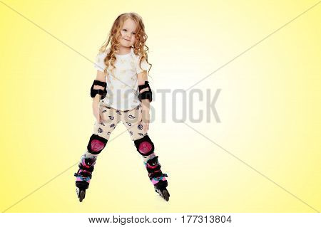 Beautiful, chubby little girl with long, blond, curly hair.Girl riding roller skates in protective gear.On a yellow gradient background.