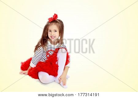Little girl in a red skirt and bow on her head.She hugged the hand to the knee.
