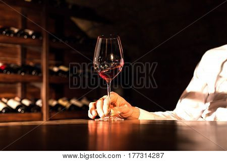 Sjot of hand holding a glass of wine on a wooden table. Wine vault location