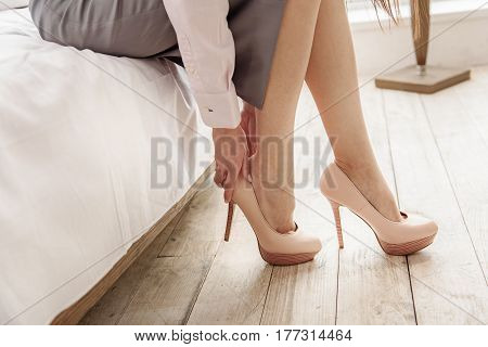 Side view of calm young female putting on shoes while locating on bed in room. Close up of her legs