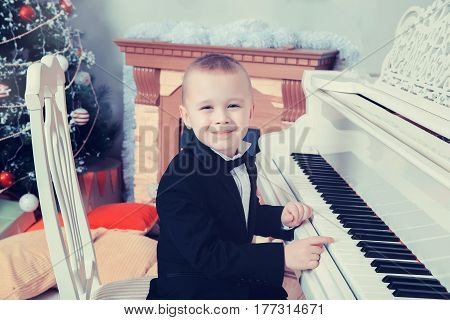 Beautiful little boy in a strict black suit , white shirt and tie.He sits at the piano keys.Creative toning of a photograph.
