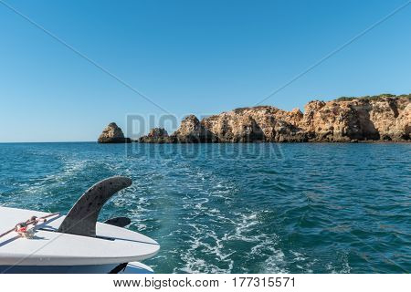 Idilic landscape with paddle surf boards. Scenic golden cliffs near Alvor Portimao. This beach is a part of famous tourist region Algarve