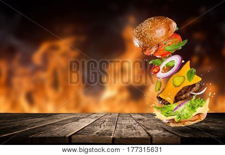 Big tasty home made burger with flying ingredients. Fire flames on background.