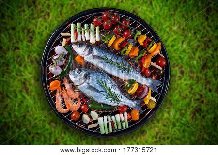 Grilled sea fishes with vegetable, skewers and prawns on a barbecue grill, top view.