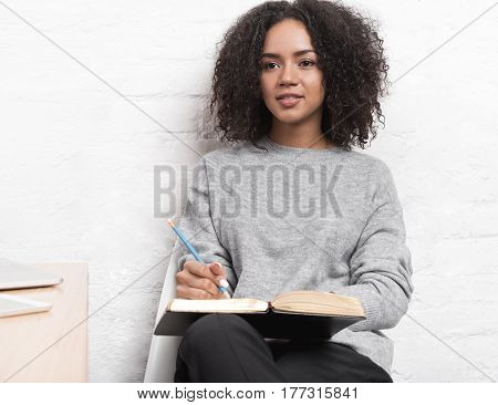 Young female blogger sitting in cafe, concentrated on new ideas