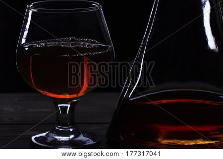 Glass And Carafe With Cognac, Whiskey On Black Wooden Table