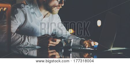 Bearded young businessman working at office at night. Man using contemporary notebook for texting message, holding smartphone on hand. Horizontal wide, bokeh effect, reflections