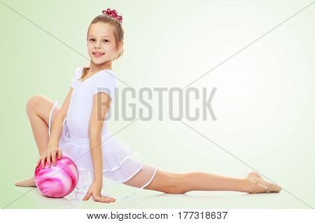 Beautiful little girl gymnast dressed in sports suits for competition, performs exercises with the ball.On a light green gradient background.