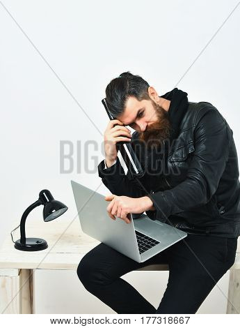 Bearded man long beard. Brutal caucasian unshaven hipster sitting on table with lamp and bottle on holding laptop in black leather jacket isolated on white studio background