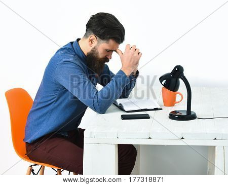 Bearded man long beard. Brutal caucasian unshaven serious hipster with moustache sitting at white wooden table with black lamp mobile phone and open notepad on it isolated on white background