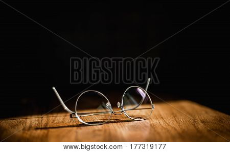 Busines like of elegant modern eyeglasses spectacles pair with thin titanium rim on office table and black background