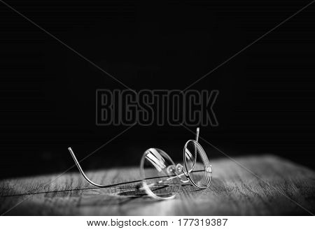 Black and white image of elegant modern eyeglasses spectacles with thin titanium rim on office table