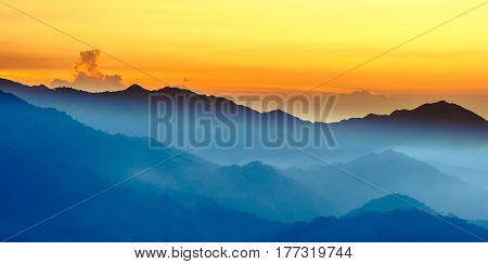 orange sunset with fog in the mountains