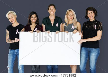 Group of women with pink ribbon and holding blank banner for breast cancer awareness poster
