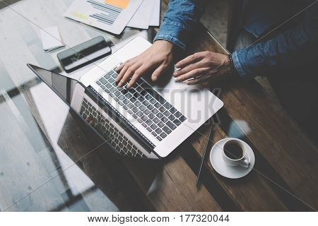 Coworker man working with laptop at office.Modern notebook, cup of black coffee and smartphone on the wooden table.Horizontal, blurred