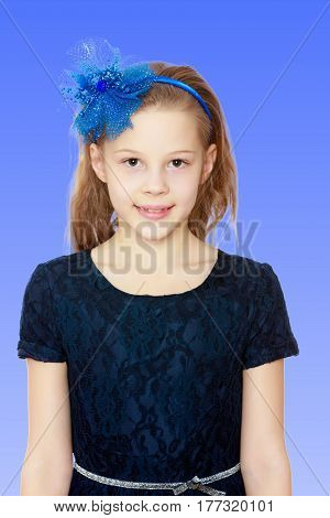 Cute Caucasian little girl In a dark blue dress and big blue bow on her head.On a bright blue gradient background.
