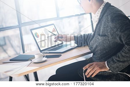 Elegant young man in eyeglasses working at office on laptop while sitting at the wooden table.Businessman anazyle graphs and diagramm on notebook screen.Horizontal, blurred background