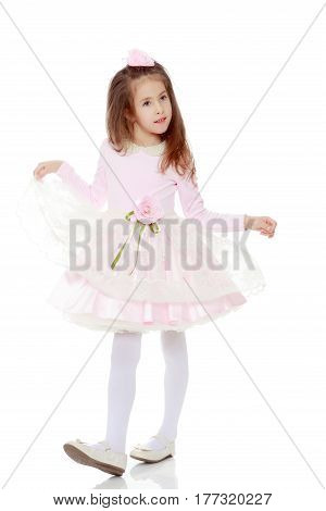 Dressy little girl long blonde hair, beautiful pink dress and a rose in her hair.She plays with her floors for her dress.Isolated on white background.