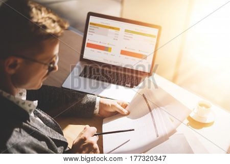 Adult businessman in eyeglasses working at sunny office on laptop while sitting at the wooden table.Man analyze document in his hands.Graphs and diagramm on notebook screen.Blurred background