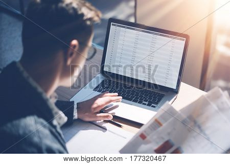Closeup view of banking finance analyst in eyeglasses working at sunny office on laptop while sitting at wooden table.Businessman analyze stock report on notebook screen.Blurred background, horizontal