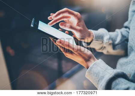 Female finger pointing on screen of mobile phone on background illumination glow bokeh light in night atmospheric.Horizontal, blurred background, flares