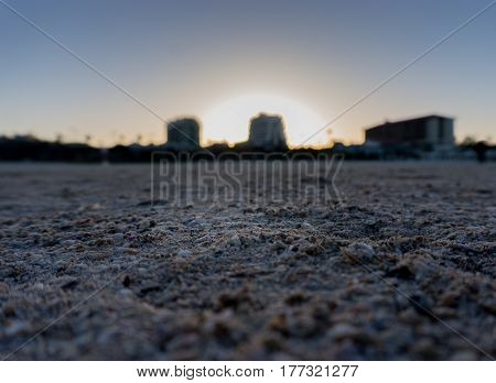 Heart shaped rock on beautiful sandy beach, clear sky, sun rays, sand in focus in the blue hour just after sunrise, Herzliya Pituah, Israel in autumn.