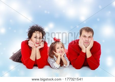 Happy young family dad mom and a little girl in bright red outfits . Family lying on the floor leaning on his hands.Blue Christmas festive background with white snowflakes.
