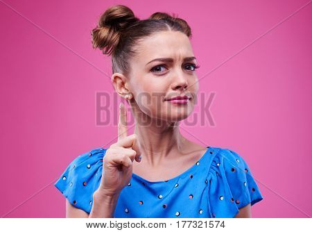 Indoors shot of reflective trendy young woman who holds index finger up. Wearing cute blue dotted dress isolated over pink background