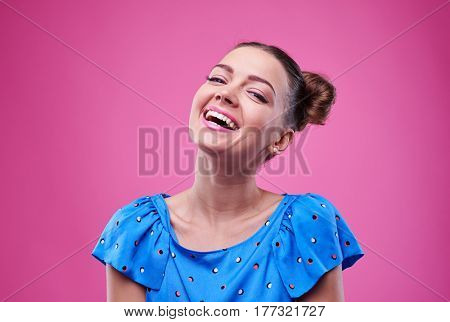 Close-up of funny girl with two buns isolated over pink background. Elated girl with open mouth laughing