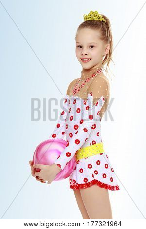 Beautiful little girl gymnast dressed in sports suits for competition, performs exercises with the ball.On the pale blue background.