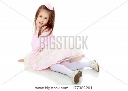Dressy little girl long blonde hair, beautiful pink dress and a rose in her hair.She lies on the floor stretching the legs forward.