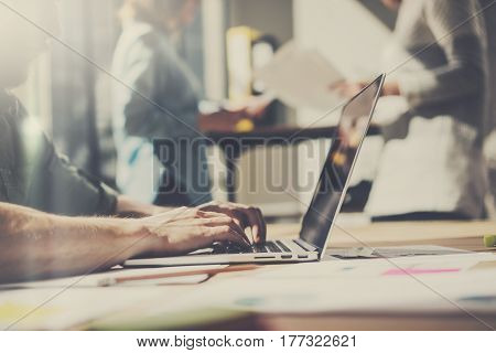 Man working at modern office.Coworker using laptop while sitting at the wooden table.Blurred background. Horizontal, color filter effect