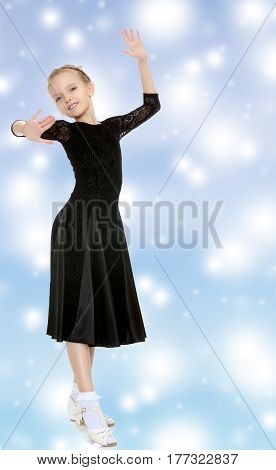 The slender little blonde girl dancer in the long dress of black color made specifically for performing .Girl graceful curves of the body.Blue Christmas festive background with white snowflakes.