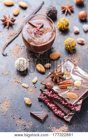 Sweet and treat, junk unhealthy food. Assortment of chocolate bar and praline truffle and mousse with spices and nuts on black moody grunge table
