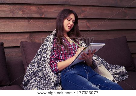 Side view of beautiful girl in casual clothes under blanket making notes while sitting on the sofa. Feeling comfortable and cosy at home. The concept of rest