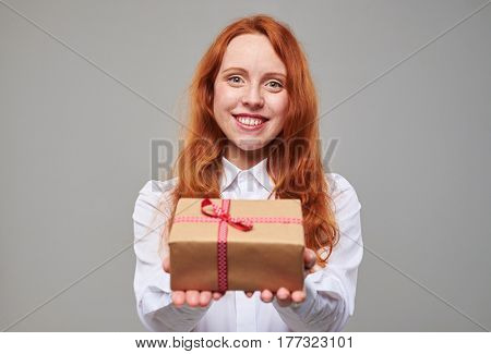 Close-up of smiling king girl with cooper hair offering a present box tied with a ribbon. Isolated over background in the studio