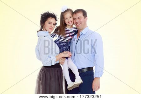 Happy young family, mom dad and little daughter.Parents keep the girl in her arms , and she hugs their neck.