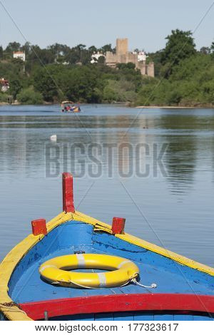 View of the Almourol castle from a colorful bow of a wooden old boat