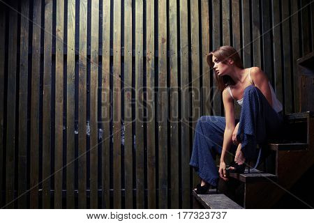 Mid side shot of the stunning woman who is sitting on the edge on the step and looking forward
