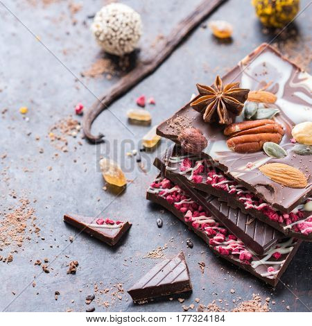 Sweet and treat, junk unhealthy food. Assortment of chocolate bar and praline truffle with spices on black moody grunge table