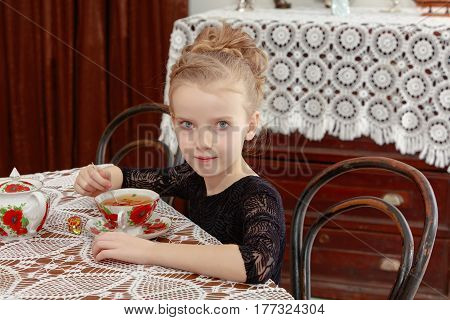 Beautiful little girl drinking tea in the interior of the fifties of the last century. Retro style.
