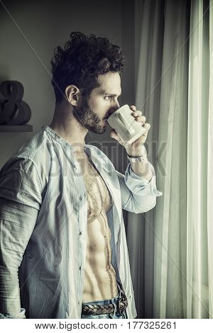 Sexy handsome young man standing with shirt open on naked chest, in his bedroom next to window curtains, holding a coffee or tea cup