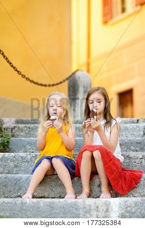 Two Cute Little Sisters Eating Ice-cream While Sitting On The Stairs On Summer Day