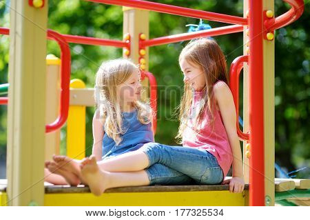 Two Cute Little Girls Having Fun On A Playground Outdoors